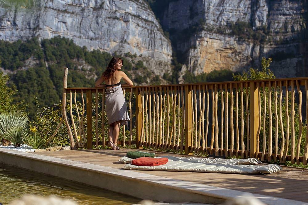 femme au bord du bassin naturel et vue sur le vercors